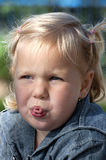 Little girl is making faces Stock Images