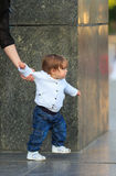 Little girl makes first independent steps being hold mother hand Stock Photo