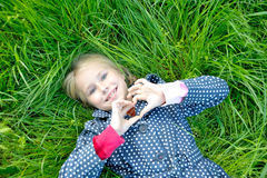 Little girl makes  gesture  form of the heart. Little blond girl lying on grass and makes a gesture in the form of the heart Stock Photos