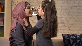 Little girl makes a make-up for her Muslim mother in hijab, makeup brush, laughing, smiling family, idyll, home comfort