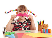 Little girl makes paper mustache Royalty Free Stock Photo