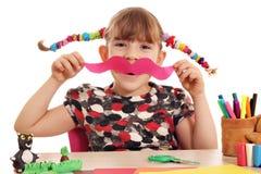 Little girl makes paper mustache Stock Image