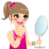 Little Girl Makeup. Cute little girl playing grown up with pink lipstick makeup while looking on mirror Stock Photo