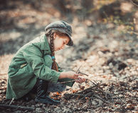 Little girl making a bonfire. Photo in vintage style Royalty Free Stock Image