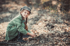 Little girl making a bonfire. Photo in vintage style Stock Image