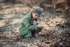 Little girl making a bonfire. Photo in vintage style Stock Photo
