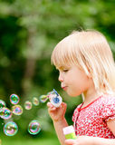 Little girl making bubbles Stock Image