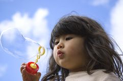 Little girl making bubbles Stock Photo