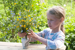 Little girl making bunch of flowers Stock Image