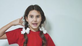 Little girl making a call me sign outdoors. Brunette hispanic girl smiling doing phone gesture with hand and fingers stock footage