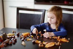 Little girl making chestnuts creatures Stock Image