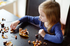 Little girl making chestnuts creatures Stock Photo