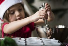 Little girl making chocolate cupcakes Stock Photography