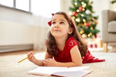 Little girl making christmas wish list at home Royalty Free Stock Photo