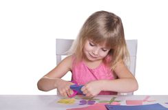 Little girl making a crafts. Little girl making a crafts with scissors and paper Stock Photography