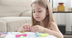 Girl playing with colored plasticine on table. Little girl making creative shape from colored plasticine stock video footage