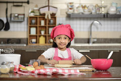 Little Girl Making Dough Stock Images