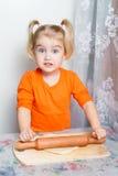 Little girl making dough in the kitchen. Little girl making dough in the kitchen with a rolling pin Stock Photo