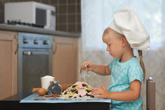 Little girl making dough in a shape of volcanoe Royalty Free Stock Photos