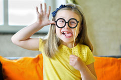 Little girl making face with funny glasses and showing her tongue Royalty Free Stock Photo