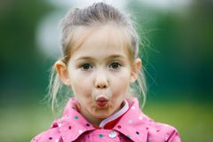 Little girl making faces for the camera. On a hiking trip with her family. Disobedience, cheerful  behavior and carefree childhood concept Royalty Free Stock Photos