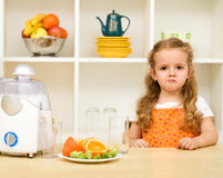 Little girl making faces - fruit juice again ?. Little girl making faces asking - fruit juice again and no junk food Royalty Free Stock Image