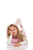 Little girl making faces. Little girl with long hair making faces on the floor. Isolated on white background Royalty Free Stock Image