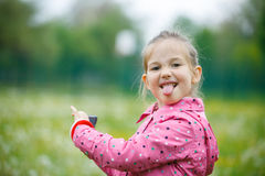 Little girl making faces and showing her tongue Royalty Free Stock Photo
