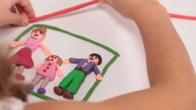 Little girl making a family and house from plasticine stock footage
