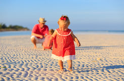 Little girl making first steps at the beach with family on background. Cute little girl making first steps on the beach with family on background Stock Image