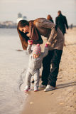 Little girl making first steps on beach with help Royalty Free Stock Photo