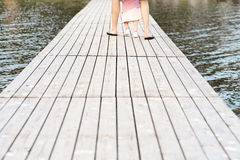 Little girl making first steps with father. Latvia. Father teaches his daughter to walk on a wooden platform on the water Stock Photo