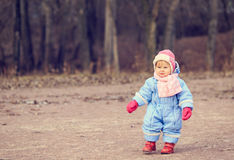 Little girl making first steps in  park Royalty Free Stock Images