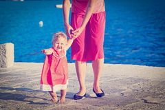 Little girl making first steps at the sea Stock Photo