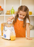 Little girl making fresh fruit juice Stock Photography
