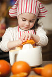 Little girl making fresh juice. Little girl making fresh and healthy orange juice with kitchen appliance Stock Image