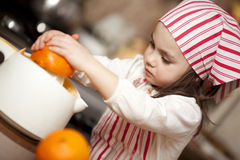 Little girl making fresh juice. Little girl making fresh and healthy orange juice with kitchen appliance Stock Photo