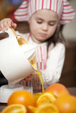 Little girl making fresh juice. Little girl making fresh and healthy orange juice with kitchen appliance Stock Images