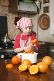 Little girl making fresh juice. Little girl making fresh and healthy orange juice with kitchen appliance Royalty Free Stock Photos