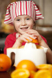 Little girl making fresh juice. Little girl making fresh and healthy orange juice with kitchen appliance Royalty Free Stock Photo
