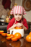 Little girl making fresh juice. Little girl making fresh and healthy orange juice with kitchen appliance Stock Photography