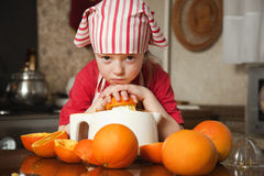 Little girl making fresh juice. Little girl making fresh and healthy orange juice with kitchen appliance Stock Photos