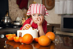 Little girl making fresh juice. Little girl making fresh and healthy orange juice with kitchen appliance Royalty Free Stock Images