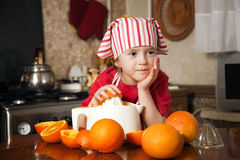 Little girl making fresh juice. Little girl making fresh and healthy orange juice with kitchen appliance Royalty Free Stock Image