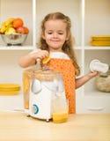 Little girl making fruit juice Royalty Free Stock Photos