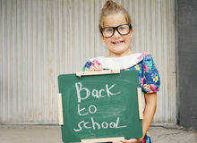 Little girl making funny face, holding Chalkboard with words Back to School. Outdoor photo Royalty Free Stock Image