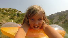 Little girl making funny faces while lying on air mattress stock video