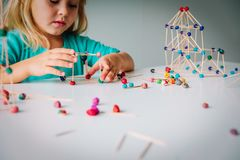 Little girl making geometric shapes, engineering and STEM. Little girl making geometric shapes from sticks and dough, engineering and STEM royalty free stock images