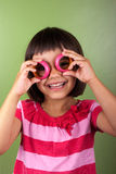Little girl making glasses with rings. Funny girl making eyeglasses with napkin rings Royalty Free Stock Images
