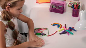 Little girl making a happy family house from modeling clay stock video